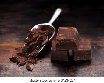 dark chocolate pieces on a wooden background and metal scoop