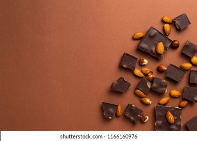 Dark chocolate pieces with roasted almonds scattered around on brown background