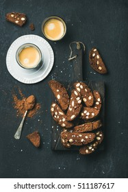 Dark chocolate and sea salt Biscotti cookies with almonds and two glasses of coffee espresso on wooden serving board over dark stone background, top view, vertical composition