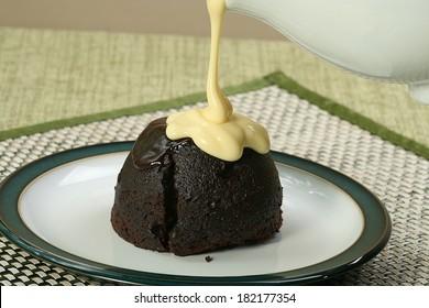 dark chocolate sponge dessert with pouring custard