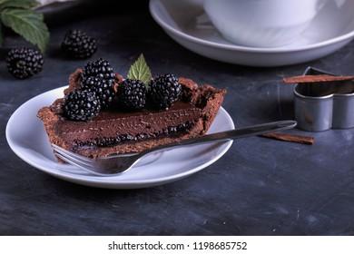 Dark Chocolate Tart with Blackberries. Chocolate Blackberry Tart. Slice of Blackberries Tart on white plate, dark background.