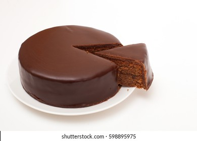 A dark chocolate tort on porcelain plate, isolated on white background