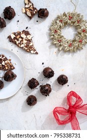 Dark chocolate truffles dusted in Oreo cookie and coffee chocolate almond bark on a white surface with a holiday wreath ornament and red ribbon bow.