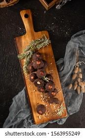 Dark chocolate truffles with hazelnuts over wooden cutting board.