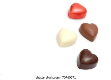 A Dark Chocolate Valentine's Heart in the Foreground with Three More Chocolate Hearts in the Background with Room for Text