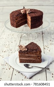 dark chocolate vegan cake with candies and cream on wooden background