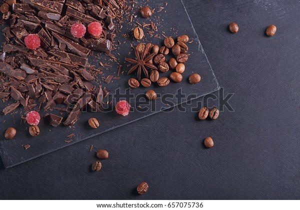 Dark chopping chocolate, black roasted coffee beans, red berries with spices on slate board over black textural background. Chocolate dessert and sweets concept. Top view with space for text.