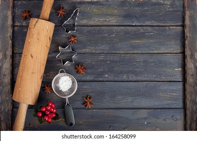 dark Christmas baking background, bake ware, cookie cutters - star and tree, sieve, sugar and a rolling pin on wooden board, mystic light,