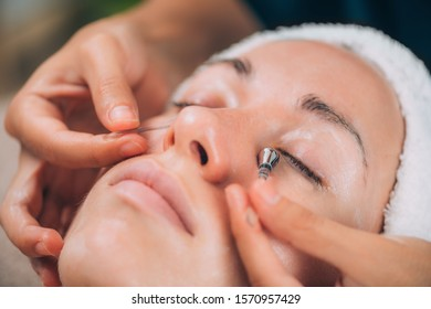 Dark Circles Face Massage. Close-up of a young woman getting lymphatic drainage face massage with sticks