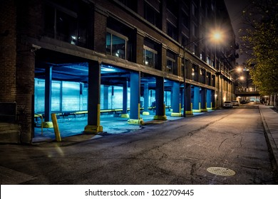 Dark city downtown street road and alley at night with an industrial warehouse loading dock.