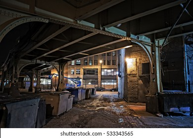 Dark city downtown urban alley at night with dumpsters and garbage, elevated train tracks and cars.