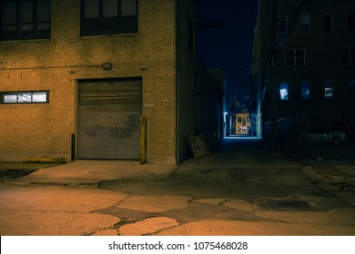 Dark city street corner and alley with an industrial building entrance at night