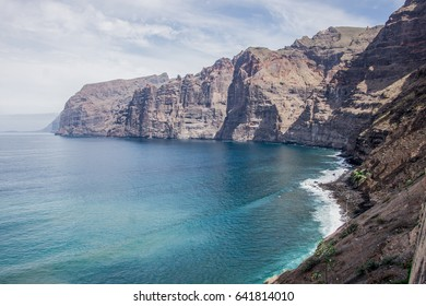Dark cliffs on Tenerife Island with the emerald waters