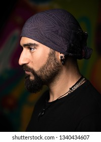 Dark close up portrait of a man with piercings and bandana.
