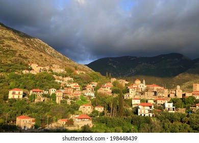Dark clouds above the mountains and Lagkada village at sunset, Peloponnese, Greece