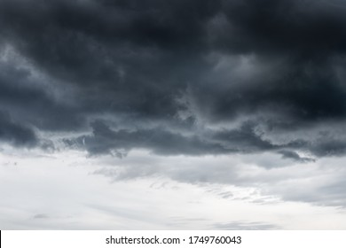 Dark clouds before heavy rain storm. On sky  covered over by clouds. A lot of lightning and strong wind. Dark clouds is look like a big black smoke from  erupting volcano but have Wind storm thunder.