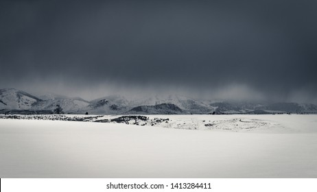 Dark clouds give way to snowfall in a rural snow-covered field during an Idaho Winter.