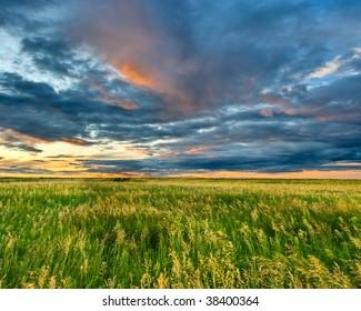 dark clouds on sunset above field