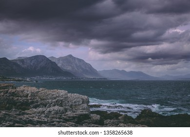 Dark clouds over the fishing village of Hermanus, with mountains in the background and some rocks and the rough ocean in the foreground, in South Africa