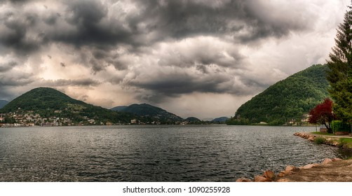 Dark clouds over the Lugano lake in a spring afternoon with mountains at the horizon, Ponte Tresa