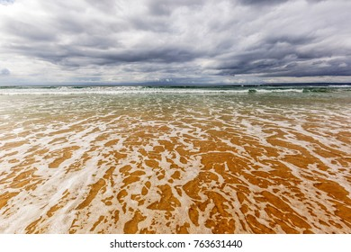 dark clouds over the ocean with waves and water washing up on a warm sandy shore