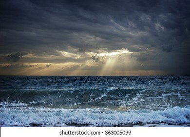 Dark clouds over stormy sea hiding sunlight in Thailand.