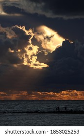 Dark clouds with rays in the center against the background of a sunset over the sea. black silhouettes of people