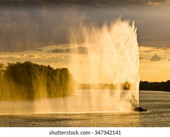 Dark clouds and strong wind create water curtain against sunset light, Ada, Belgrade, Serbia