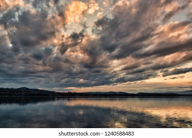 dark clouds at the sunset over the lake of Varese in a quiet autumn landscape with hills at the horizon
