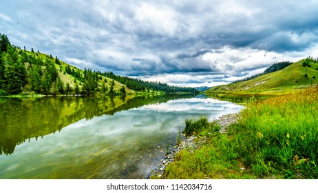 Dark Clouds and surrounding Mountains reflecting on the smooth water surface of Trapp Lake, located along Highway 5A between Kamloops and Merritt in British Columbia, Canada