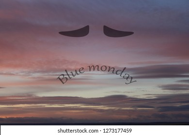 dark cloudy sky, with sad smile and watery eyes. Blue monday text