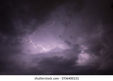 A dark cloudy sky with thunder lightning bolt strike