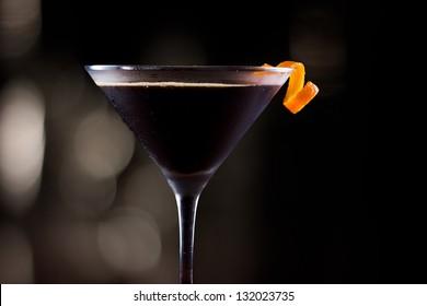 dark cocktail garnished with an orange twist on a dark bar setting