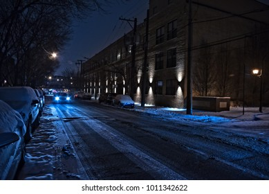 Dark and cold Chicago winter street with snow and ice and an oncoming car at night.