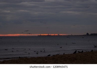 Dark, cold and cloudy sunrise at the beach with view of the sea, port and harbor in the distance. Red sunlight.