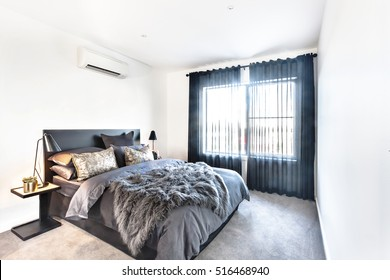 Dark color modern bed decoration in a hotel or house, including a table with lamp and shiny vase next pillows