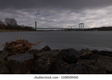 Dark color - Panorama on the Rhine with rocks in the foreground and view over the Rhine to the Rodenkirchen bridge. A storm rages over the city.