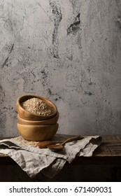 Dark composition with brown rice in front of old wall. Free space
