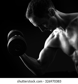 Dark contrast black and white silhouette of young muscular fitness man. Bodybuilder with beads of sweat training in gym. Working out with dumbbells on black background