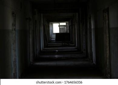 A dark corridor in an abandoned building. A cluttered corridor in ruins. Abandoned building. Horror. Dark room. Long passage.
