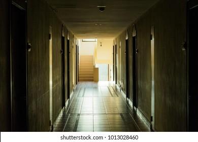 Dark corridor with cabinet doors and window light