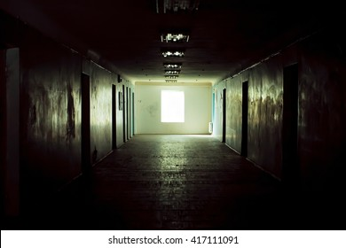 Dark corridor with cabinet doors and window light