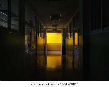 Dark corridor with doors and yellow light.