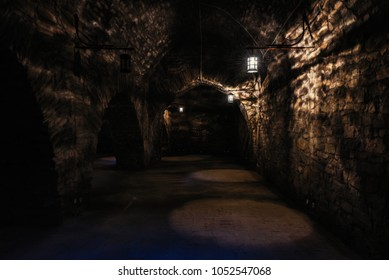 Dark corridors of old time castle dungeon light with few lamps