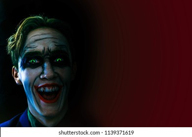 A dark, creepy joker screaming laughter in the dark. Halloween party. Comics heroes. Copy space for text.