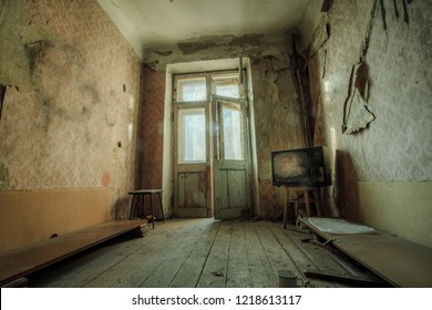 Dark creepy messy room with broken TV set in abandoned house.