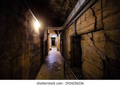 Dark creepy old corridor of underground bunker or prison.