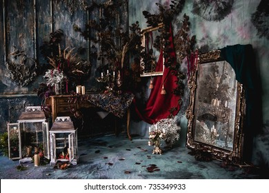 dark decor with dried flowers, vases, chandeliers, textured fabrics against the wall with a golden frame, a wooden table in a luxurious royal Victorian style,candles in old lanterns