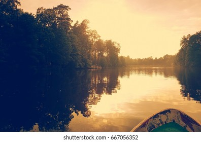 Dark deep forest background with yellow orange sky with old retro soviet boat at sunset time yesterday. Calm sunny water surface, nobody. Pushcha-Voditsa, Kiev, Ukraine. Toned vintage image.