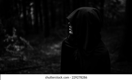 Dark demon in dark forest. Grim reaper in search of his victim. Death coming for his soul. Woman devil in black cape and hood